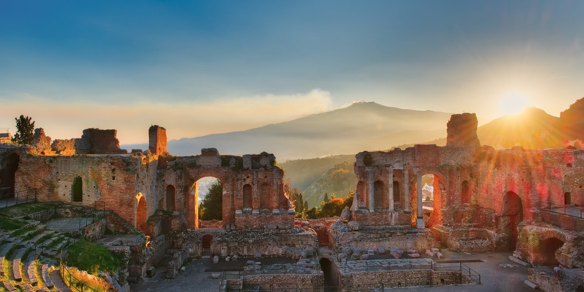 Particular of Ancient theatre of Taormina  Sicily Italy with Etna  erupting volcano at sunset
